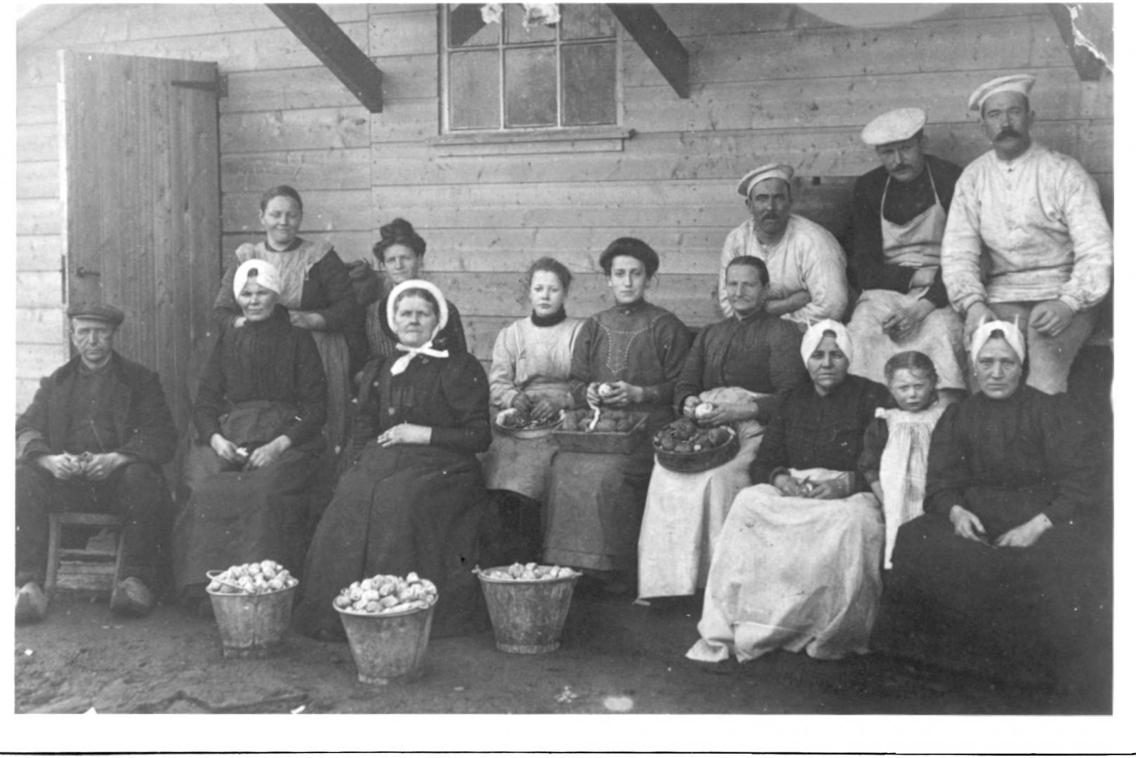De aardappelschillers voor de militairen voor de barak op het Drilleveld in 1939. Zittend van links naar rechts Toon de Kruif, mw. van Leersum, mw. K Verbeek ( met rond muts), ??., mw. Van Ramele, Mie Ransdorp en mw. Rijdes. Het meisje is onbekend.